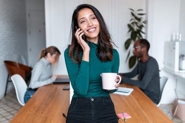 オフィスで携帯電話で話している若いインドのビジネス女性起業家のショット。バックグラウンドで、彼女の同僚は働いています。
