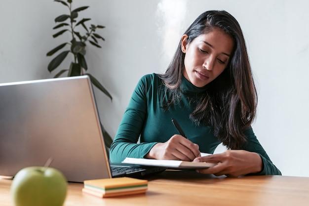 オフィスでラップトップを使用して作業しているときに彼女の議題に書いている若いインドのビジネス女性起業家のショット。