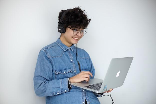彼女のラップトップを保持し、楽しいビデオを見ながら画面上で元気に見ているキーボードで手を維持している短いトレンディなヘアカットを持つ若い素敵なポジティブな巻き毛のブルネットの女性のショット