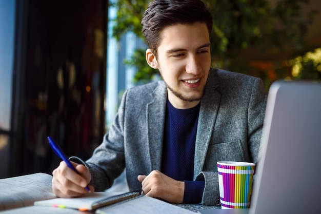 Снятый молодого студента сидя на таблице и писать на тетради. молодой студент учится в кафе.