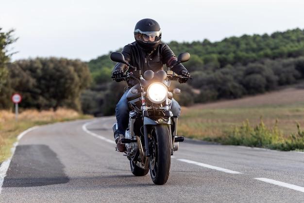 Снимок байкера молодого человека, весело проводящего время за рулем пустого шоссе в поездке на мотоцикле.