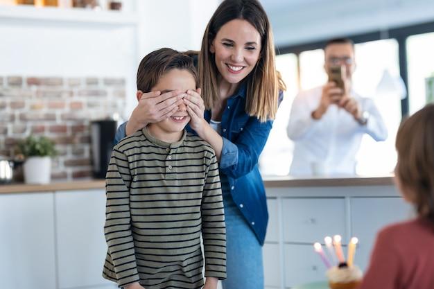 집에 있는 부엌에서 아들에게 생일 케이크를 가져다주는 동안 어린 어머니가 아들의 눈을 가리고 있는 장면.