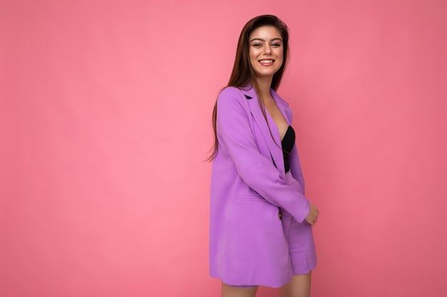 Выстрел молодой позитивной счастливой привлекательной брюнетки в стильном фиолетовом костюме, изолированном на розовом