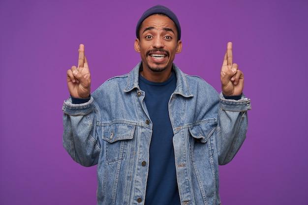 紫色の壁に立って、興奮して見ながら幸運のために彼の指を交差させる黒い肌を持つ若いかなりひげを生やした茶色の髪の男のショット
