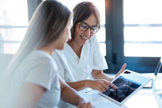 Выстрел из врача-гинеколога молодой женщины, показывающий беременной женщине ультразвуковое сканирование ребенка с цифровым планшетом в медицинской консультации.