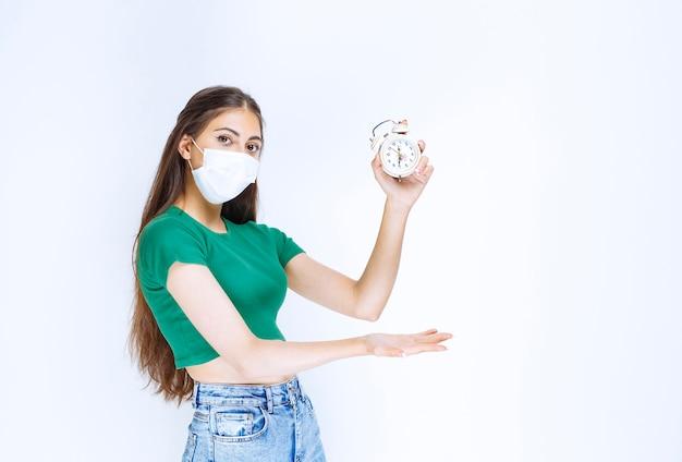 目覚まし時計を示す医療マスクの若い女性のショット。