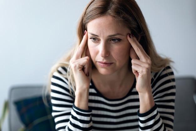 自宅のリビングルームのソファに座っている頭痛のある若い女性のショット。