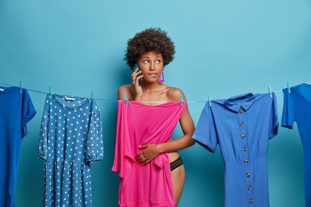 Shot of pensive dark skinned young woman has phone conversation, gets consultancy what to wear on informal meeting, poses near rope with dresses, isolated on blue wall. clothes concept.