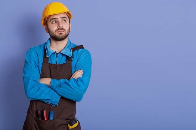 Shot of pensive dissatisfied construction worker dresses protective yellow helmet and brown apron, stands with arms folded