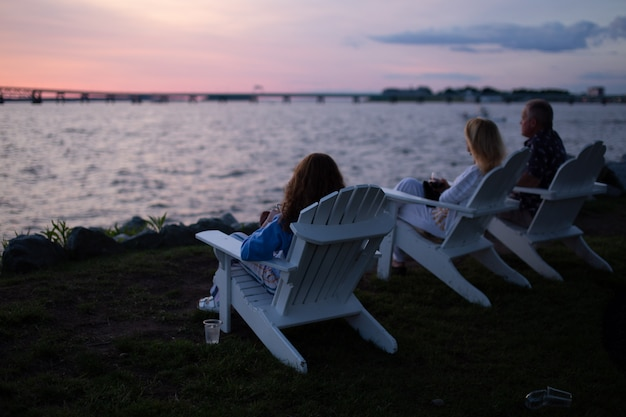 Shot of people sitting on white chairs across body of water