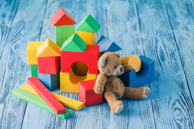 Shot of pile of various wooden blocks and toy bear