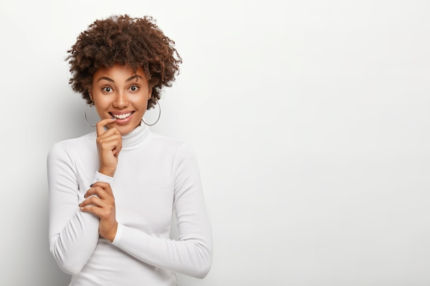 Shot of pleasant looking dark skinned curly woman holds finger near mouth, smiles broadly, looks positively , has partly crossed arms, wears earrings and turtleneck, isolated on white