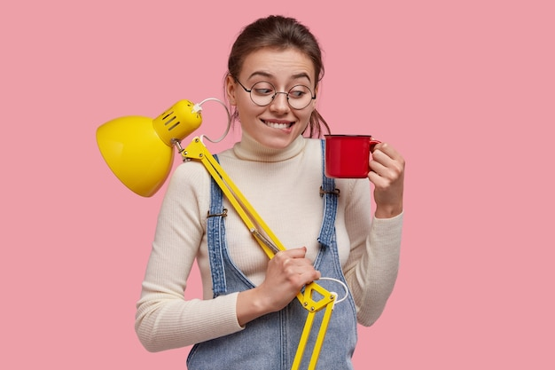 Shot of pleasant looking lady looks joyfully at cup of coffee, wears round spectacles, carries yellow desk lamp