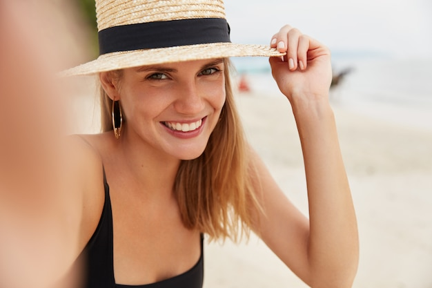 Shot of pleasant looking smiling woman in straw hat, has shining smile, poses for selfie against ocean background, being in high spirit as spends summer vacation in paradise place with lover