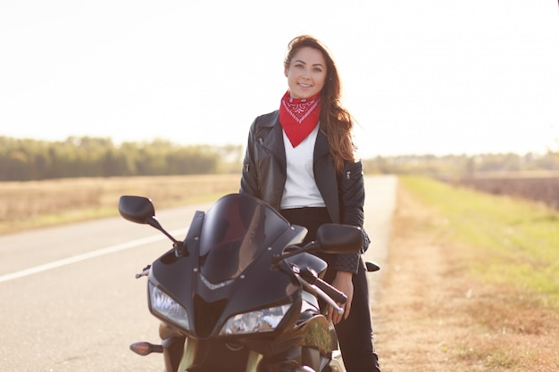 Shot of pleasant looking woman biker sits on fast black motorbike, wears red stylish bandana and leather jacket, travels alone