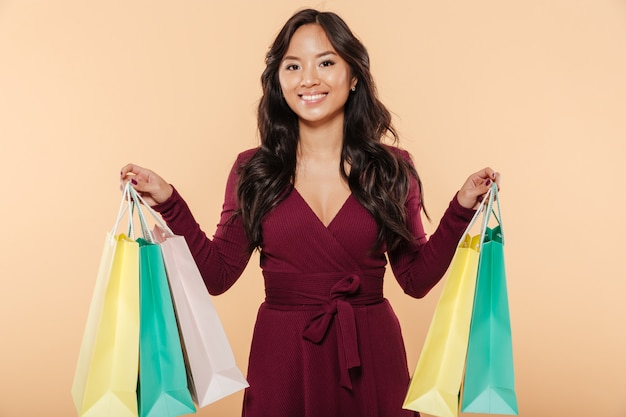 Shot of pleased asian female in pretty maroon dress posing over beige background holding packs with purchases after shopping