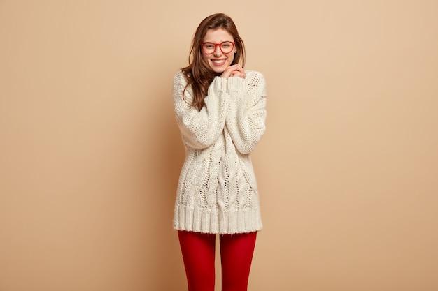 Inquadratura di una donna europea soddisfatta prova piacere, gode di complimenti, sorride ampiamente, mostra denti bianchi, indossa un maglione a maniche lunghe e collant rossi, posa contro il muro beige. concetto di emozioni