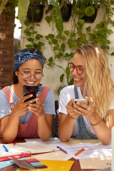 Colpo di donne di razza mista compiaciute che realizzano progetti insieme, dipendenti dalle moderne tecnologie, scambiano foto