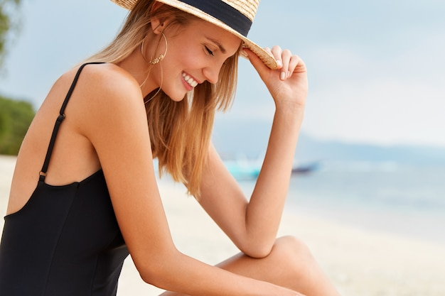 Shot of pleased shy female tourist looks happily down, wears summer hat and bathing suit, poses against blue ocean view, recreats during hot summer weather outdoor. people and recreation concept
