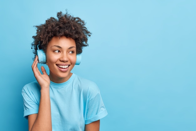 Shot of pleased teenage girl with afro hair listens music via wireless headphones from playlist dressed in casual clothes isolated over blue wall copy space for your advertisement