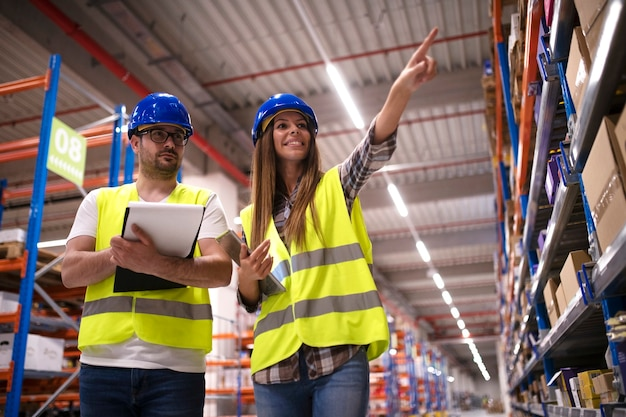 Shot of positive cheerful warehouse workers checking inventory on shelves together and controlling distribution of products in large storage area