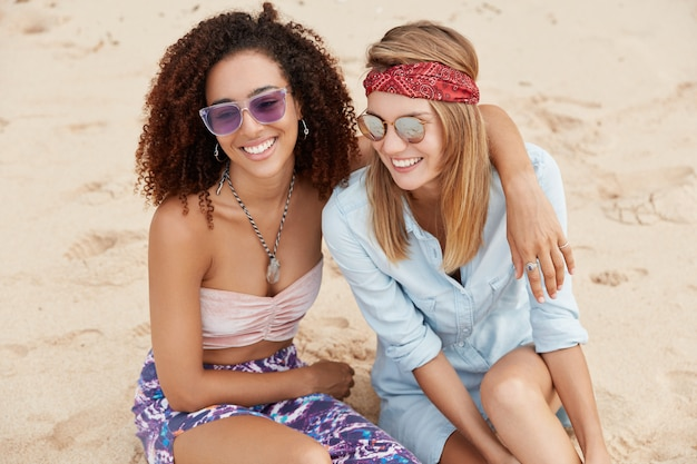 Shot of positive young females cuddle on beach, wear fashionable clothing, have summer rest at beach, admire wonderful sea or ocean views, have happy expressions. homosexual relationship concept