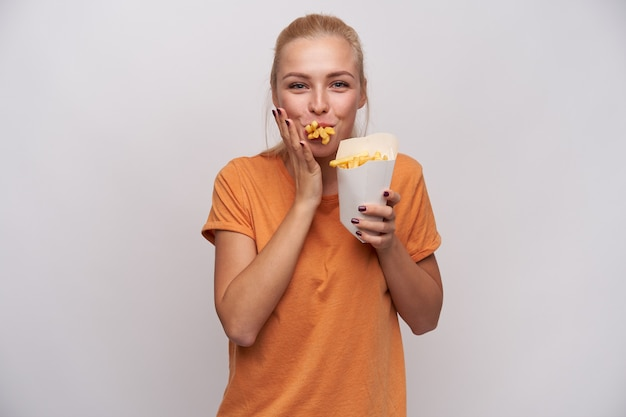 Shot of positive young pretty blonde female with casual hairstyle looking cheerfully at camera with mouth full of french fries, being hungry and happy to get meal, isolated over white background