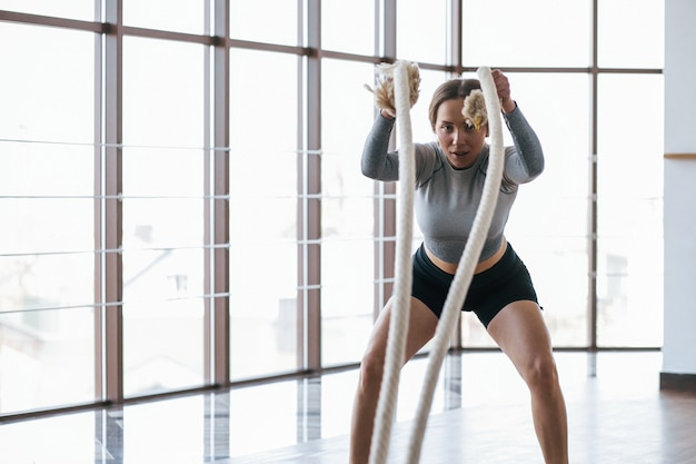 Shot of pretty female doing exercises with ropes. sportive young woman have fitness day in the gym at morning time
