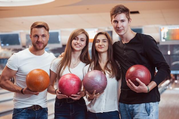 Colpo di belle persone prima della partita. i giovani amici allegri si divertono al bowling durante i fine settimana