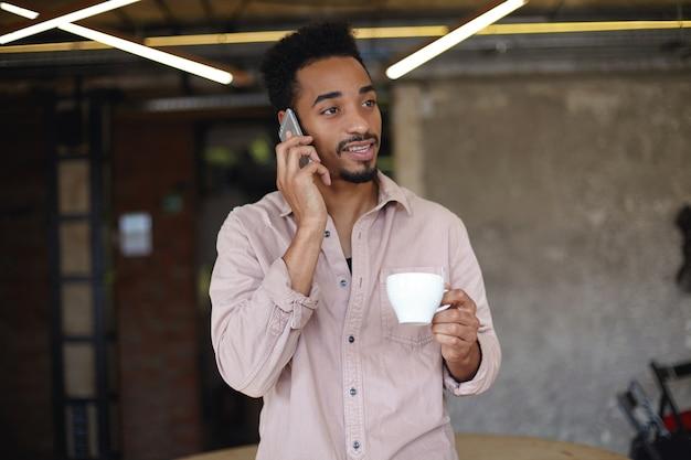 Colpo di uomo barbuto piuttosto giovane con la pelle scura in pausa pranzo e bere caffè nella caffetteria della città, effettuare chiamate con il suo smartphone e guardare da parte con viso calmo