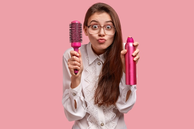 Shot of pretty young female model makes grimace, holds hairbrush and spray, has curious expression, going to make hairstyle