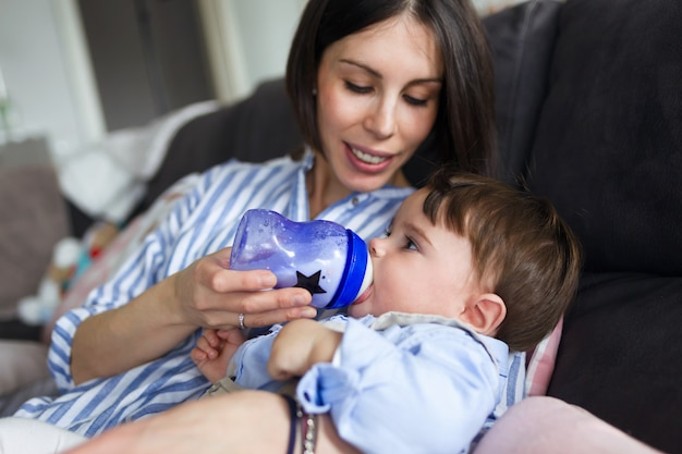 Shot of a pretty young mother feeding her baby with milk on feeding bottle in the living room of home.