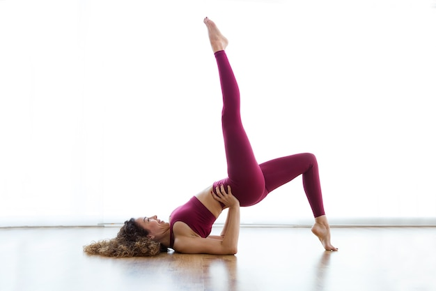 Shot of pretty young woman practicing yoga at home. eka pada setu bandha sarvangasana pose.