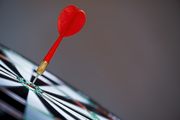 Shot red darts arrows in the target center on dark background. business target concept.