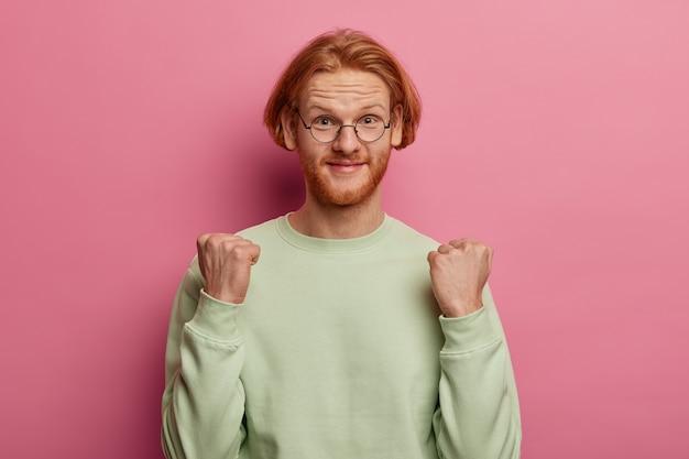 Colpo di uomo caucasico allo zenzero sollevato stringe i pugni, anticipa che sia successo qualcosa di buono, indossa occhiali rotondi e maglione, isolato su un muro rosa pastello. concetto di linguaggio del corpo