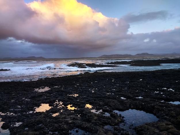 Colpo di una spiaggia rocciosa durante il tramonto a fuerteventura, spagna.