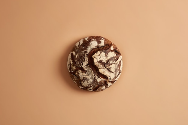 Above shot of round baked delicious bread based on sourdough, gluten free, beige studio background. healthy food, dieting and nutrition concept. cooking balanced food. whole grains, agriculture.
