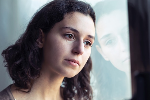 Shot of sad young woman crying while looking through the window at home.
