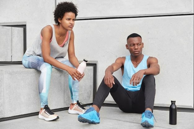 Shot of self confident black woman and man dressed casually, sit at stairs near wall, drink fresh water not to feel thirsty, have rest, lead healthy lifestyle, have exercises outside. horizontal view