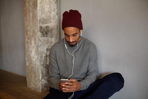 Colpo di uomo barbuto dalla pelle scura attraente serio con smartphone digitando un messaggio e guardando lo schermo con viso concentrato, appoggiato sul muro bianco, vestito con abiti casual