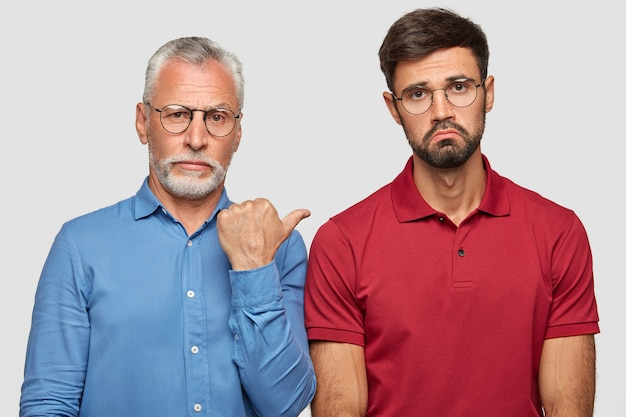 Shot of serious grey haired male pensioner indicates at his son, shows his direct heir of property. displeased unshaven young caucasian man being unhappy after quarrel with mature father