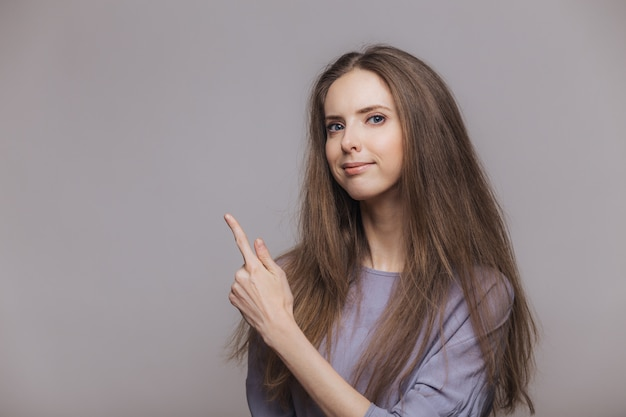 Shot of serious pleasant looking brunette female with blue eyes, dressed casually, points with index finger at blank copy space