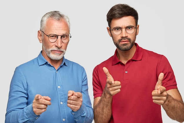 Shot of serious self confident male partners of different age point directly, make choice, wear formal blue shirt and red bright t-shirt, pose together against white wall.