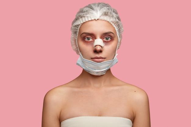 Inquadratura di una donna seria che indossa maschera e cappello medico, ha rinoplastica, preapres per blefaroplastica, ha lividi intorno agli occhi, guarda seriamente la telecamera,