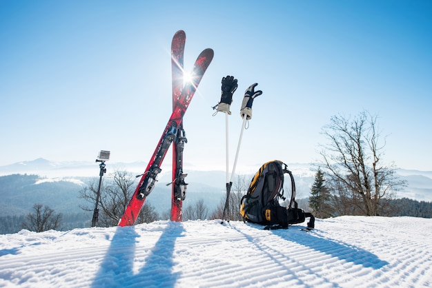 Shot of skiing equipment - skis, backpack, sticks, gloves and action camera on monopod