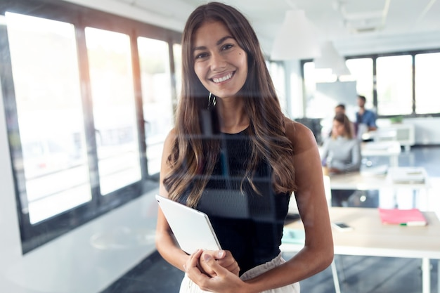Shot of smiling young businesswoman looking at camera while standing and holding her digital tablet in the modern startup office.