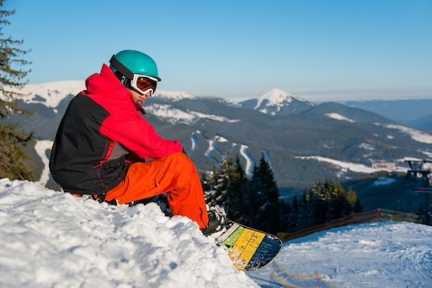 Shot of a snowboarder enjoying beautiful view of snowy mountains, winter ski resort
