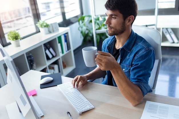 Shot of software developer drinking coffee while working with computer in the modern startup office.