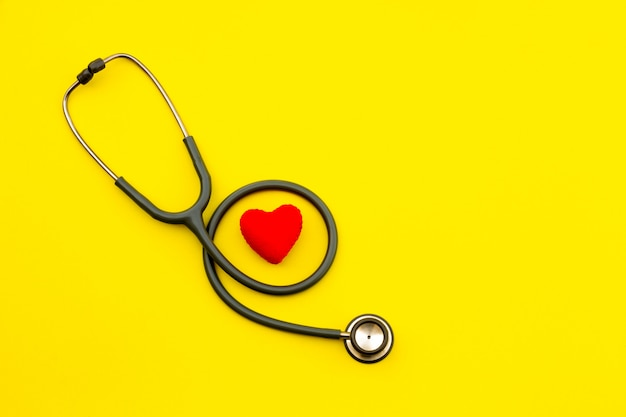 Above shot of a stethoscope puts on the left side of a table on a yellow background.