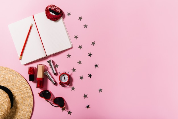 Shot of straw wide-brimmed hat, set of cosmetics, sunglasses and notebook on pink wall,